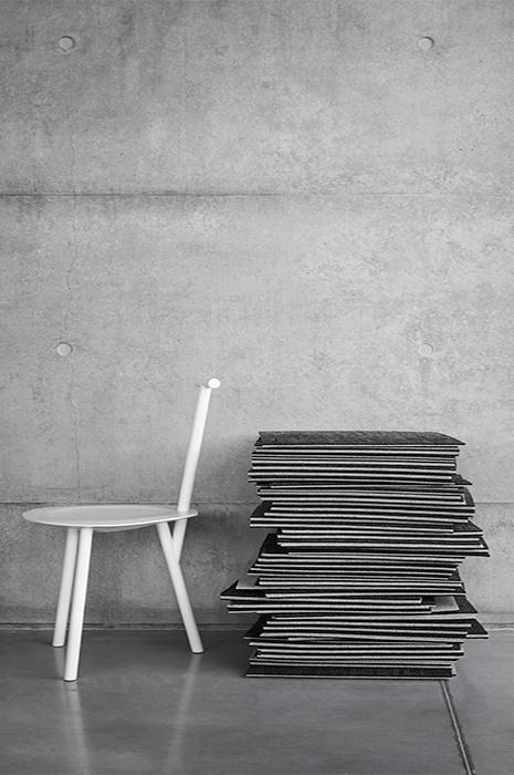 Gestapelte Teppichfliesen neben modernem Stuhl