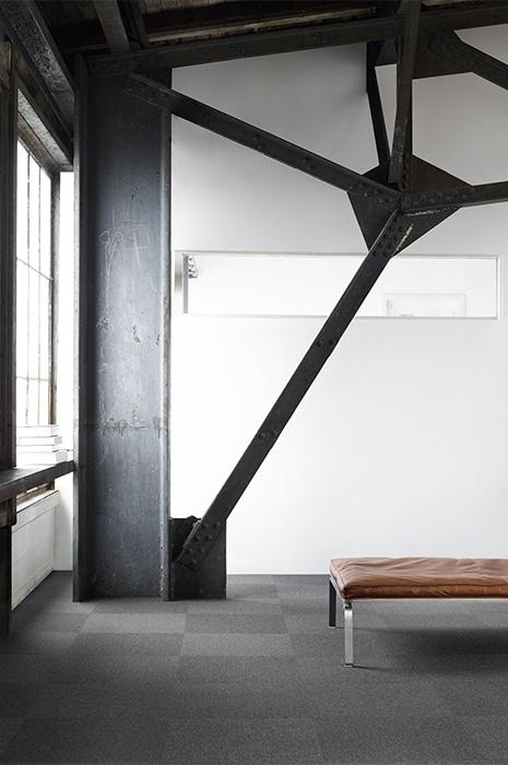 Industrieller Raum mit Sitzbank und grauen Teppichfliesen