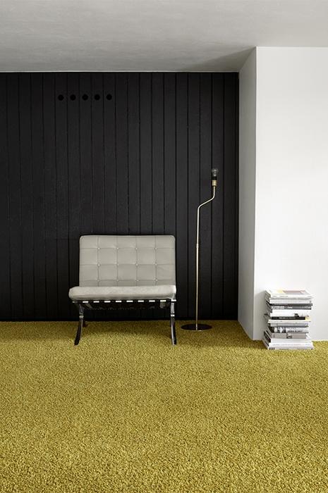 Akustik Teppich - Minimaltisch designter Raum mit  Sitzmögklichkeit und gelbem Teppich, der die Akustik verbessert