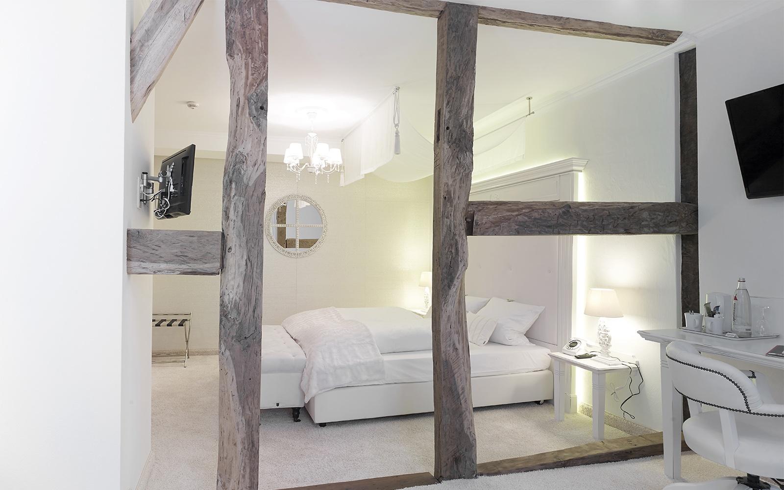 Akustik Teppich - Gemütliches Hotelzimmer in hellen Farben und Holzbalken im Raum , verschieden Stoffe und heller weißer Teppich sorgen für eine gutes Raumgefühl