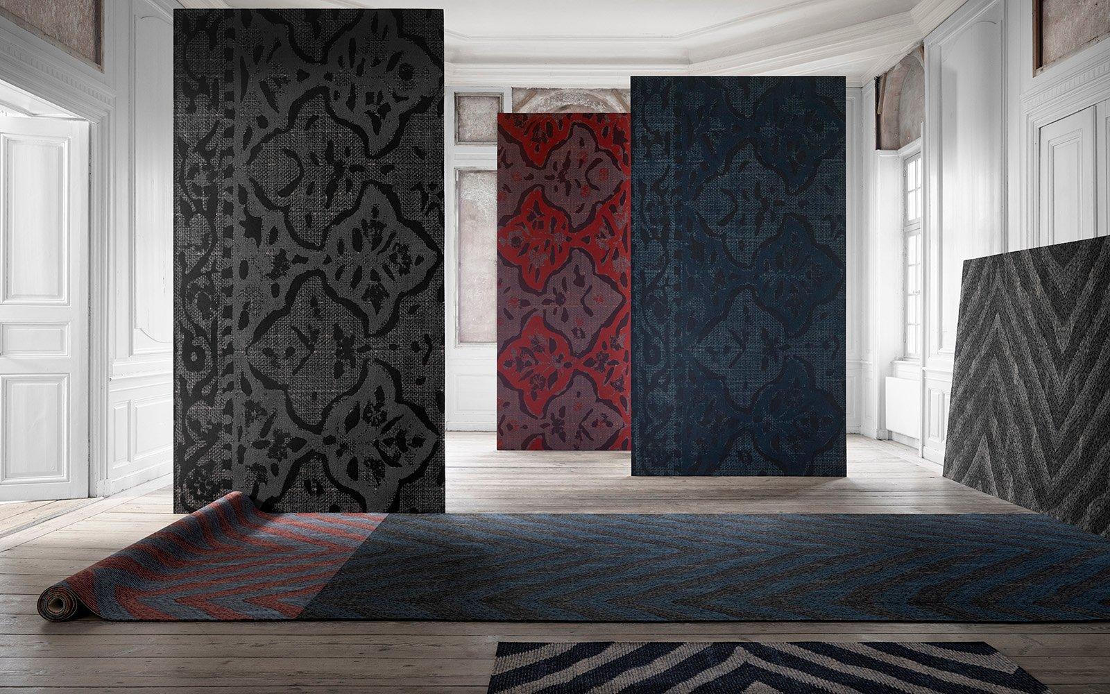 Altbauzimmer mit von der Decke hängenden und auf dem Boden liegenden Teppichbahnen mit verschiedenen Mustern