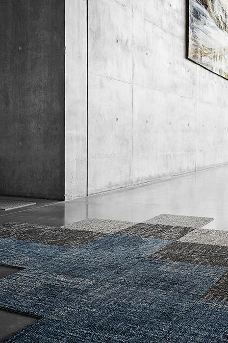 Teppichfliesen oder Teppichboden: Verschiedenfarbige, vereinzelnd ausgelegte Teppichfliesen im Raum mit industrieller Betonwand