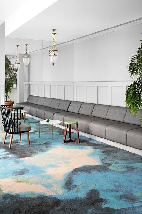 Teppichfliesen oder Teppichboden: Einladende und helle Sitzecke mit grauen Sofas und auffallend bunten Teppich Bahnenwahre