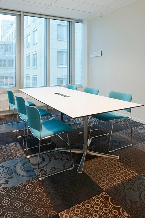 Teppichfliesen oder Teppichboden: Büro Besprechungszimmer mit großem Tisch und türkisen Stühlen und verschieden gemusterten Teppichfliesen