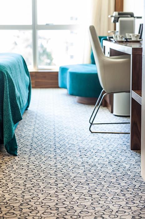 Teppichfliesen oder Teppichboden: Gemütliches Hotelzimmer mit hellem gemusterten Teppich Bahnenwahre von ege und türkisen Möbelakzenten