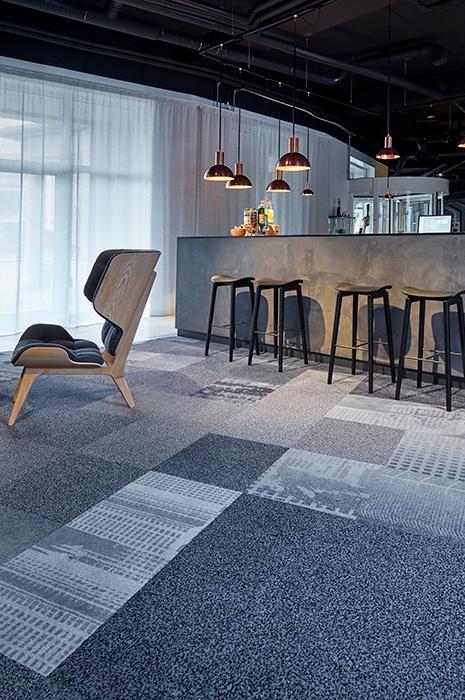 Teppichfliesen oder Teppichboden: Modern designte und minimalistisch eingerichtete Bar in grau Tönen und graugemusterten Teppichfliesen von ege