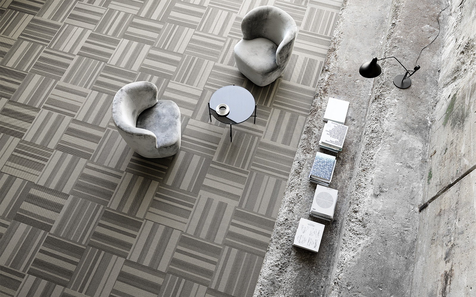 Two chairs in a plain setting room with grey striped carpet tiles
