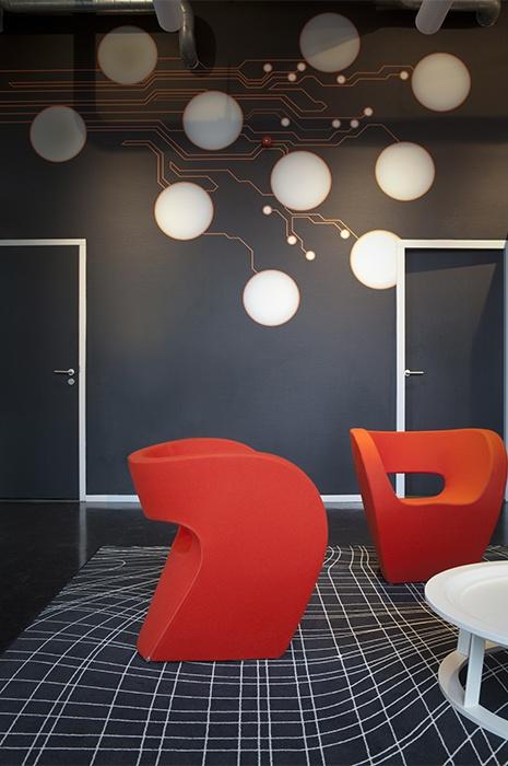 Moderne Räumlichkeiten mit roten ausgefallenen Sesseln und gestreiften dunklem Teppich von ege