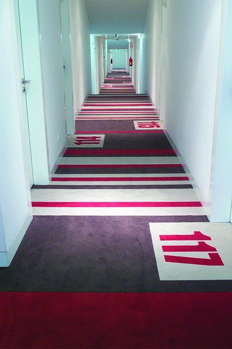 Sonderangefertigter Teppich für Hotelflur mit Zimmernummern vor der Tür
