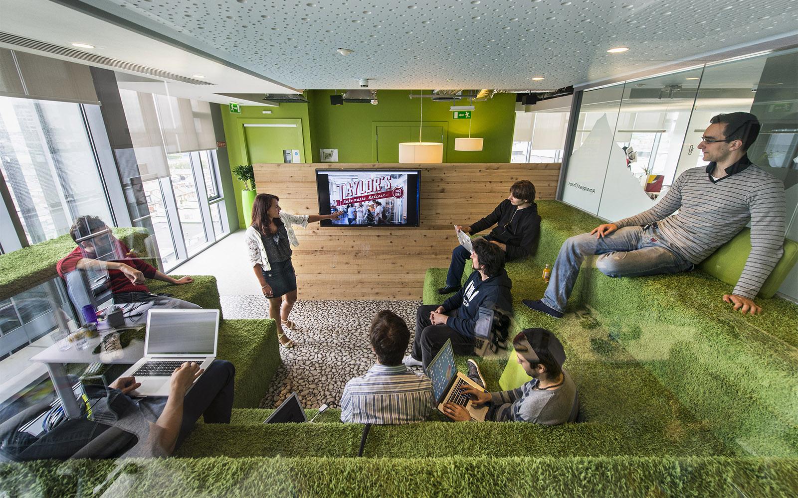 Grün eingerichtete Räumlichkeiten mit Teppichüberzogenen Stufen als Sitzmöglichkeiten von ege im Google Campus Dublin