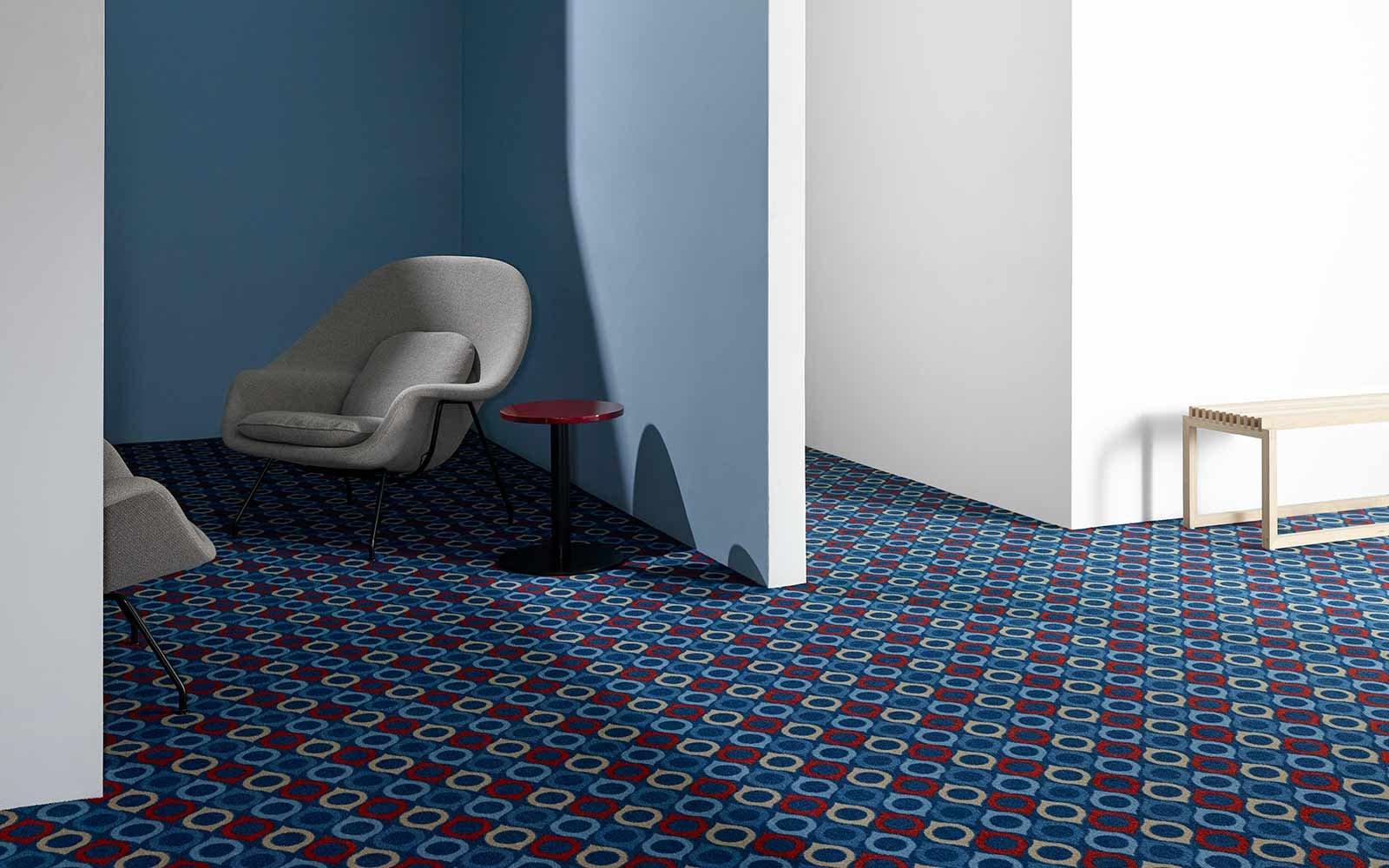 Minimalistischer moderner Raum mit Teppich in blauem und rotem Muster