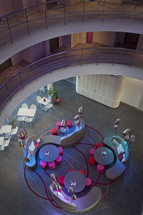 Hotelteppich: Geschwungene Linien in lila und pinken Farben auf dem Teppich verbinden die ebenfalls geschwungenen Sitzgruppen zu einem einheitlichen Konzept